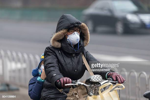 woman wearing mouth mask with filter against air pollution, beijing - chinese mask stock photos and pictures