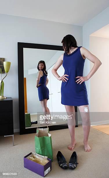 Woman wearing new dress, looking in mirror