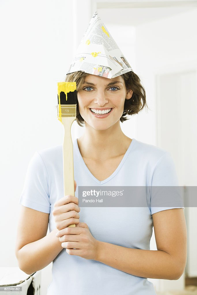 Woman wearing newspaper hat with paintbrush : Stock Photo