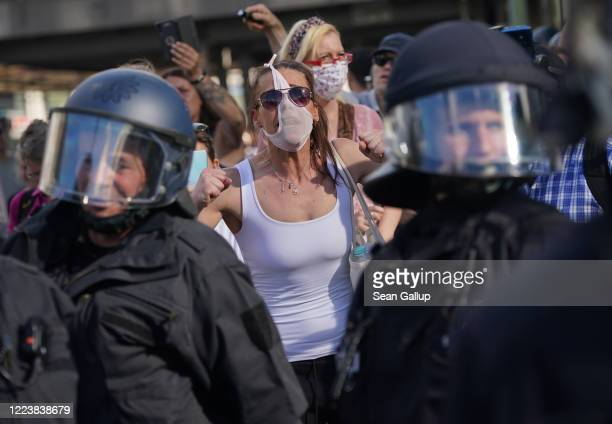 A woman wearing panties as a face mask derides riot police among protesters gathered to rally against coronavirus restrictions on Alexanderplatz...
