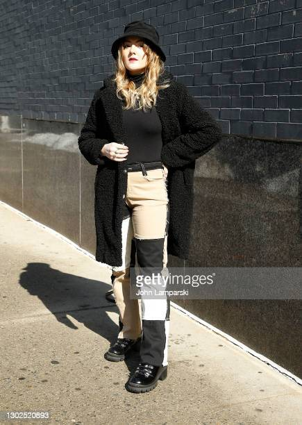 Woman wearing pants with sewn on patches and a black coat and bucket hat arrives at Spring Studios during New York Fashion Week on February 16, 2021...