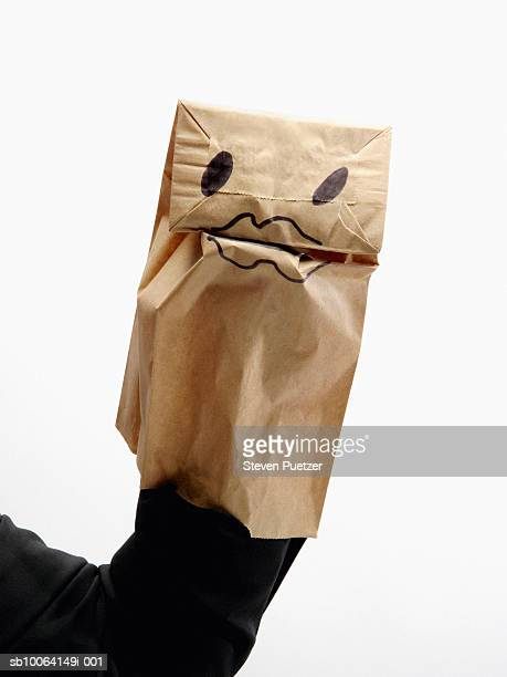 Woman wearing paper bag puppet on hand, close-up of arm and hand