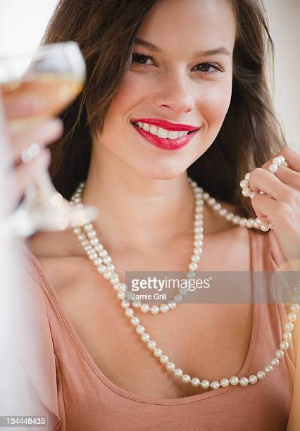 Woman wearing pearls, holding glass of champagne