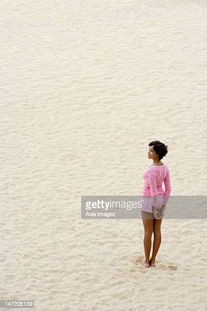woman wearing pink and standing on sand