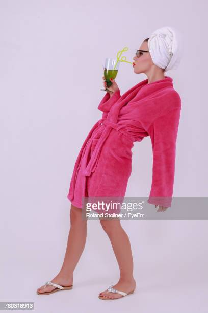 Woman Wearing Pink Bathrobe While Standing Against White Background