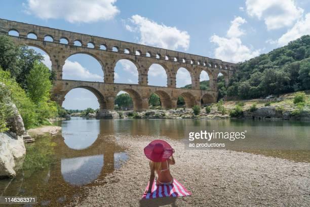 woman wearing pink hat sunbathing by pont du gard in vers-pont-du-gard, france - pont du gard stockfoto's en -beelden