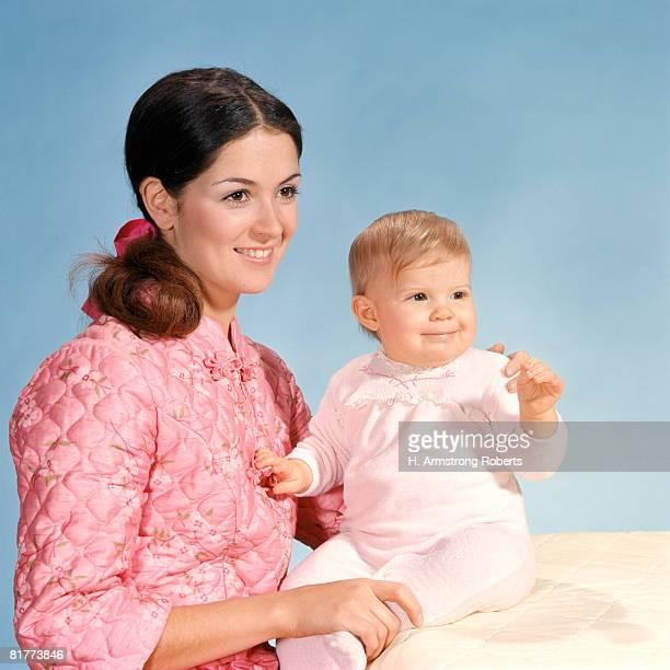 Woman wearing pink satin robe holding baby, portrait.