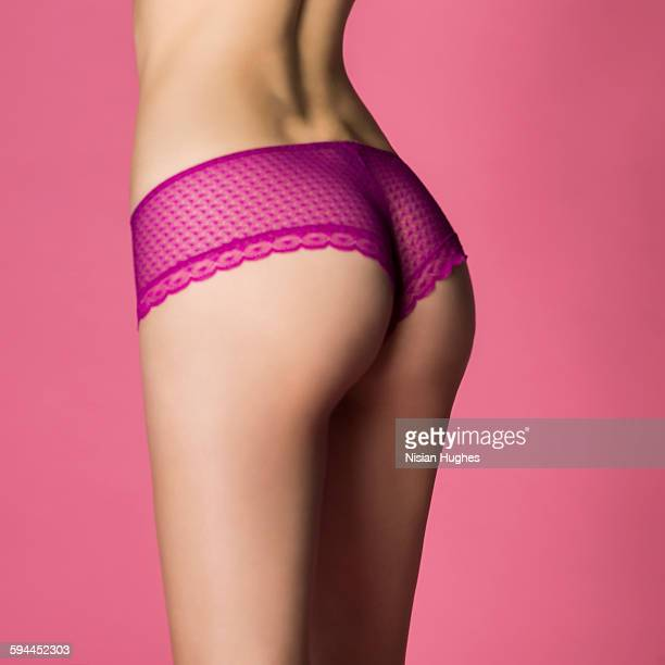 woman wearing pink silk panties on pink background - fesses culotte photos et images de collection