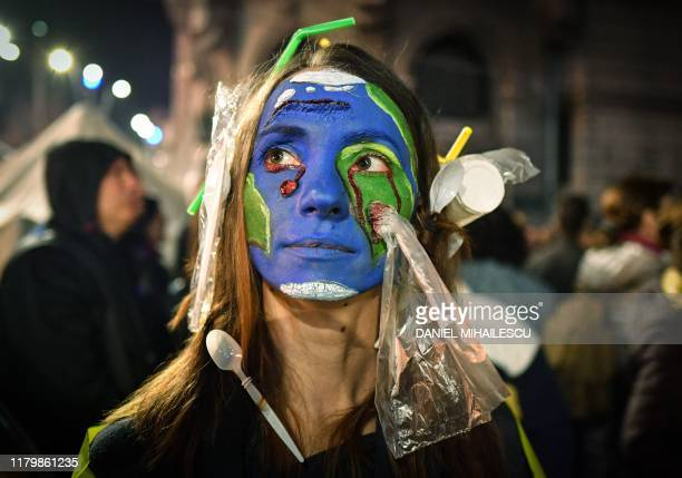A woman wearing plastic on her hair and with her face painted with earth colors demonstrates during a protest against illegal logging in the forests...