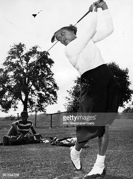 A woman wearing plus fours taking a golf swing with a young boy watching her Washington DC 1938