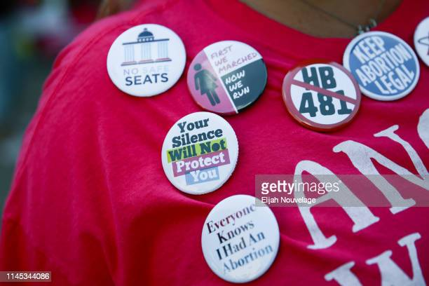 A woman wearing political buttons attends a protest against recently passed abortion ban bills at the Georgia State Capitol building on May 21 2019...