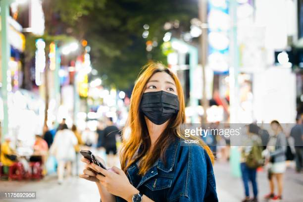 woman wearing pollution mask while using phone - cloth face mask stock pictures, royalty-free photos & images