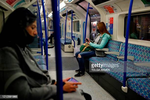 Woman wearing PPE , including a face mask as a precautionary measure against COVID-19, sits on an almost empty London Underground Tube train, in the...