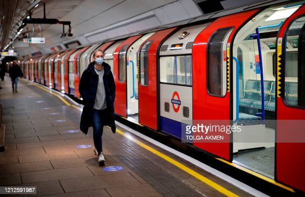 Woman wearing PPE , including a face mask as a precautionary measure against COVID-19, walks along the platform alongside a London Underground Tube...