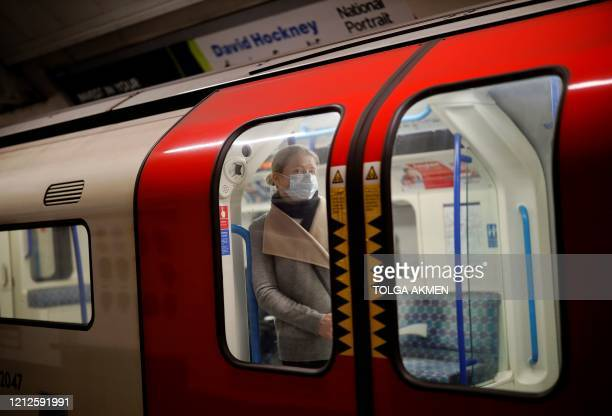 Woman wearing PPE , including a face mask as a precautionary measure against COVID-19, stands inside a London Underground Tube train, in the morning...