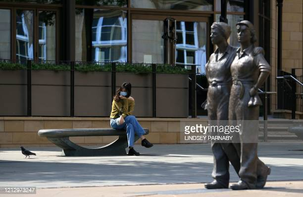 Woman wearing PPE , including a face mask as a precautionary measure against COVID-19, sits on a bench in Sheffield, northern England on May 14...