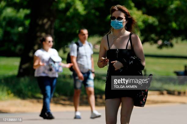 Woman wearing PPE , including a face mask as a precautionary measure against COVID-19, walks in the afternoon sunshine in Hyde Park, London, on May...