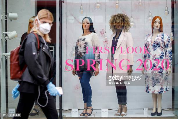 Woman wearing PPE , of a face mask as a precautionary measure against COVID-19, walks past an Evans clothing store, closed-down due to coronavirus,...