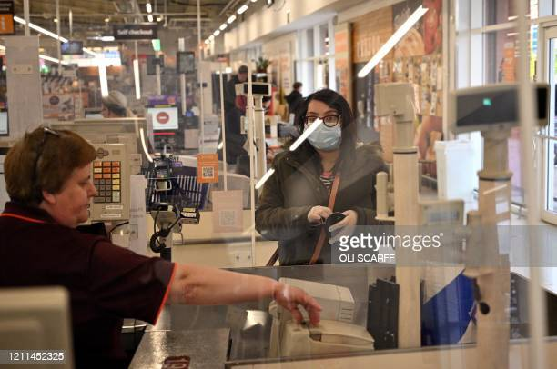A woman wearing PPE of a face mask as a precautionary measure against COVID19 stands behind a perspex screen as she is served by a worker at a...
