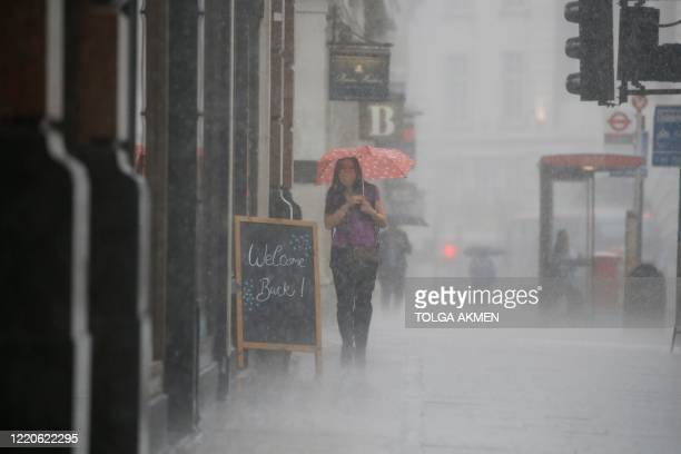 Woman wearing PPE , of a face mask or covering as a precautionary measure against COVID-19, shelters under an umbrella they are caught in a downpour...