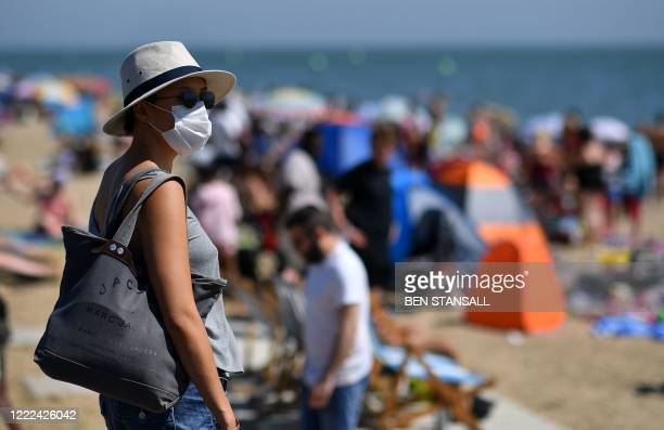 Woman wearing PPE , of a face mask or covering as a precautionary measure against spreading COVID-19, arrives on the beach in the sea in Southend on...