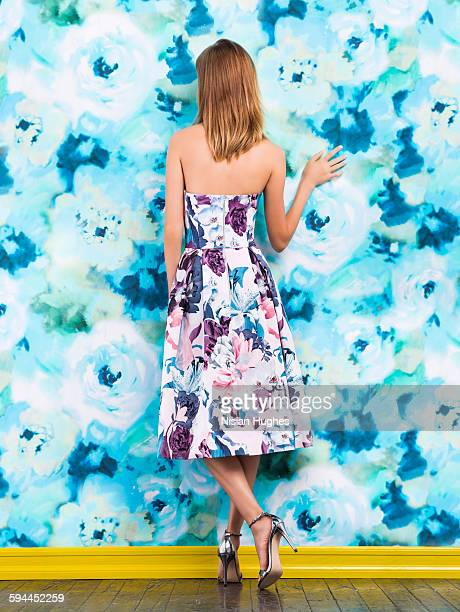 Woman wearing print dress against print background