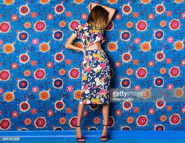 woman wearing print dress against print background - robe à motif floral photos et images de collection