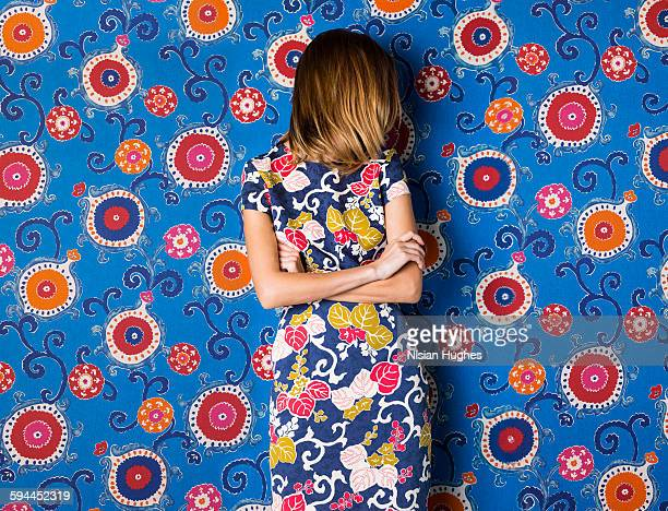 Woman wearing print dress against print background