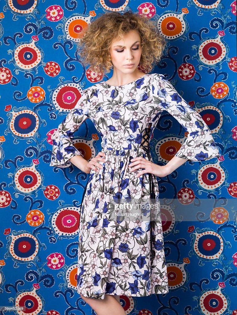 Woman wearing print dress against print background : Stock-Foto