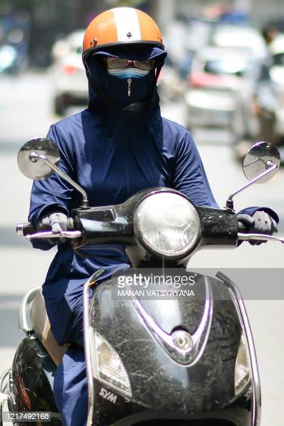 Woman, wearing protective clothing to shield from the sun, rides a scooter as the temperature soars in Hanoi on June 4, 2020.
