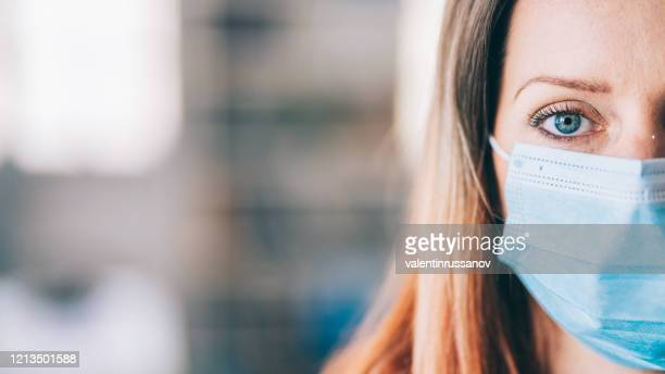 woman wearing protective face mask in the office for safety and protection during covid-19 - organised group stock pictures, royalty-free photos & images