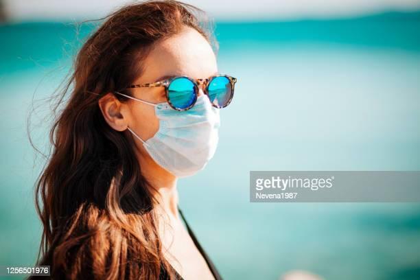 donna che indossa una maschera protettiva sulla spiaggia. vacanze estive dopo la crisi pandemica del coronavirus. - annullamento foto e immagini stock