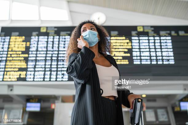 woman wearing protective face mask talking on smart phone at airport - airport stock pictures, royalty-free photos & images