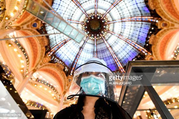 Woman wearing protective face shield shops at the Galeries Lafayette on the first day of the reopening of the luxury general store, on May 30 in...