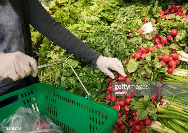 woman wearing protective gloves shopping in the supermarket. - stellalevi stock pictures, royalty-free photos & images