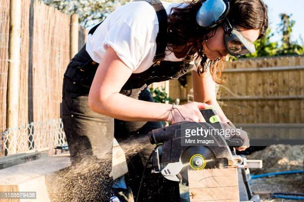 woman wearing protective goggles and ear protectors holding circular saw, cutting piece of wood on building side. - carpenter stock pictures, royalty-free photos & images