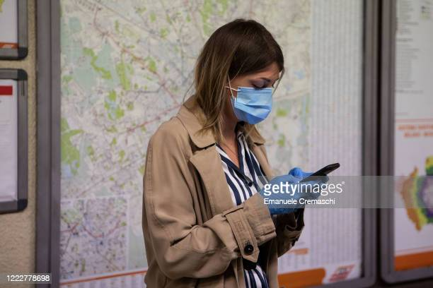 A woman wearing protective mask and gloves uses a mobile phone while waiting for a train at M1 underground line Cadorna station on May 04 2020 in...