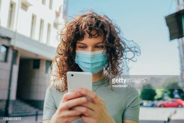 woman wearing protective mask and using smartphone in city - odessa crisis stock pictures, royalty-free photos & images
