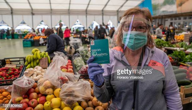 Woman wearing protective mask, gloves and a visor holds a guide for diabetics, a high risk group, while shopping in the Mercado da Vila, the city...