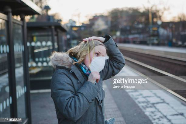woman wearing protective mask on train station platform - coronavirus winter stock pictures, royalty-free photos & images