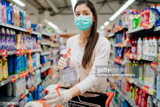woman wearing protective mask preparing for virus pandemic spread quarantine.hygiene, cleaning and disinfection products.preventive measures and protection.supply shopping during the epidemic. - terrified stock pictures, royalty-free photos & images