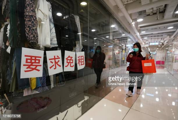 A woman wearing protective mask walks by a store at Causeway Bay on March 31 2020 in Hong Kong China