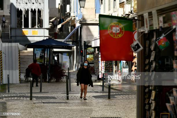 Woman wearing protective mask walks near the Baixa district, Lisbon. 07 May 2021. Portugal added, in the last 24 hours, more than 406 new cases and...