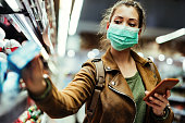 Woman wearing protective mask while using cell phone and buying food in grocery store during virus epidemic.