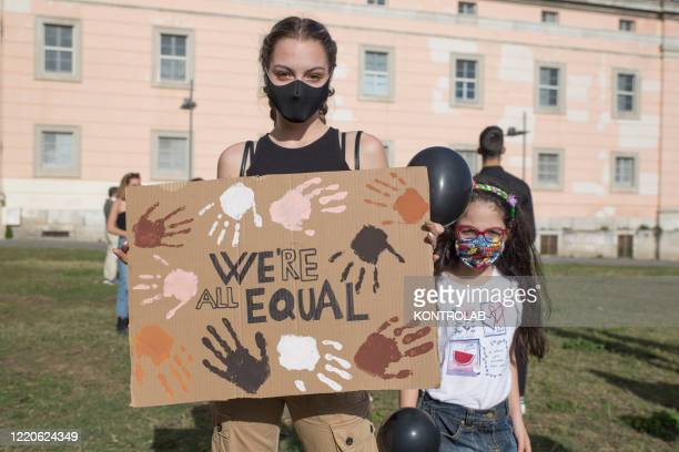 "Woman wearing protective mask with a girl holds a banner writing ""we're all equal"" during the silent flashmob in front of the Royal Palace of Caserta..."