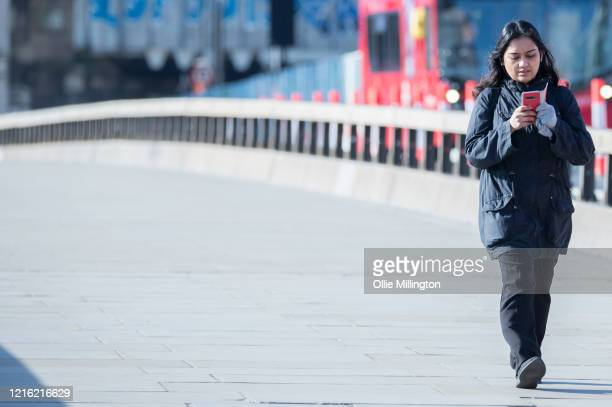 A woman wearing protetive latex gloves crosses the River Thames as the London Bridge looks empty during rush hour on March 31 2020 in London England...