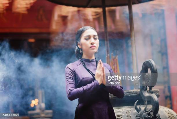 Woman wearing Purple Aodai praying in a Pagoda at Cholon, Saigon
