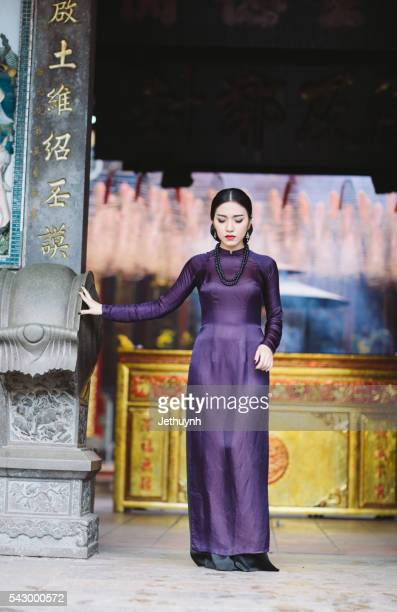 Woman wearing Purple Aodai standing in front of a Pagoda Cholon