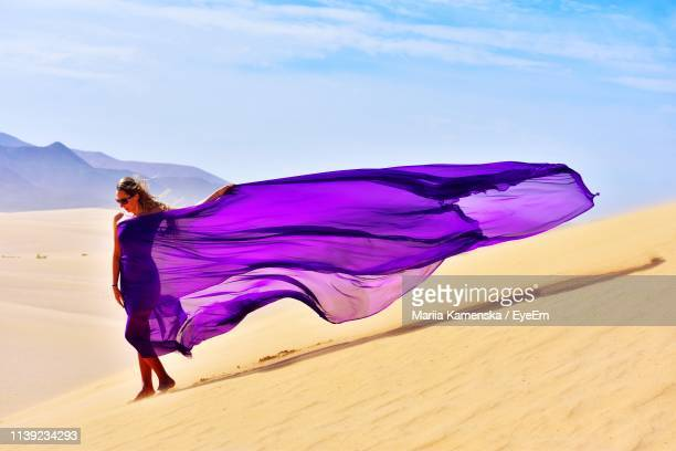 woman wearing purple dress while standing at desert against sky - purple dress stock pictures, royalty-free photos & images