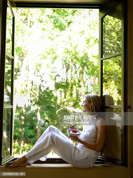 Woman wearing pyjamas sitting on window sill eating breakfast, smiling